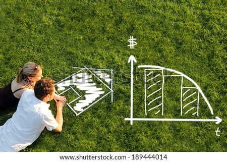 A Couple in meadow planing mortage lending for a house - stock photo