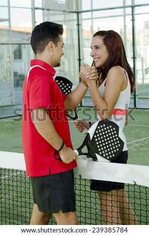 A couple in paddle tennis court ready for friendly match - stock photo