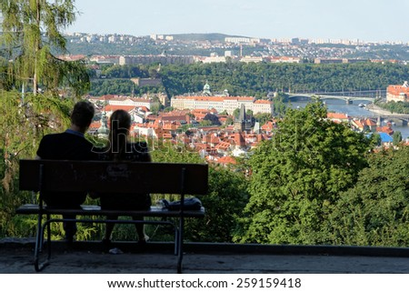 A couple is enjoying the great panorama of the city of Prague, Czech Republic, from Petrin Hill. - stock photo