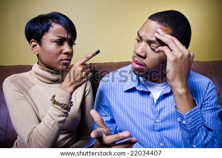 A couple is fighting on a couch and the girl is pointing her finger accusingly at him. - stock photo