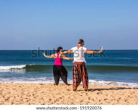 A couple is performing qigong exercises at the beach of Goa