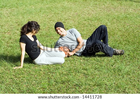 A couple is sitting on the grass in a park.  The man and the woman are looking at each other.  They are holding a basketball and smiling at each other.  Horizontally framed photo. - stock photo