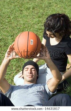 A couple is sitting on the grass in a park.  The woman is looking at the man and the man is resting on the womans lap.  The man is holding a basketball above his chest.  Vertically framed photo. - stock photo