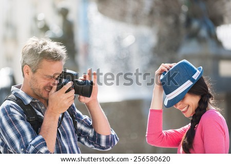A couple is taking photos in the city center. The grey hair man with a beard and a black backpack is taking a closed picture of the smiling woman with a blue hat . She is hiding behind her hat. - stock photo