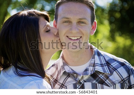 A couple kissing on the cheek