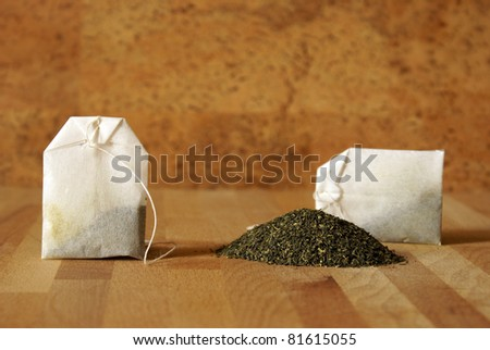 A couple of bags are next to a pile of green tea leaves.