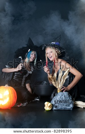 A couple of beautiful young women witches on Halloween - stock photo