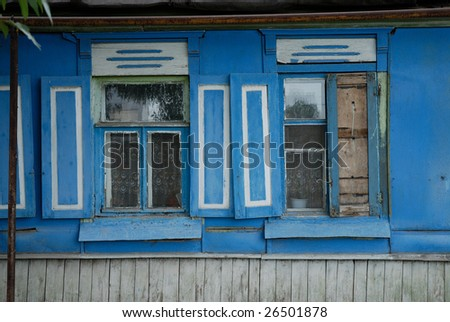 A couple of blue aged windows on wooden wall