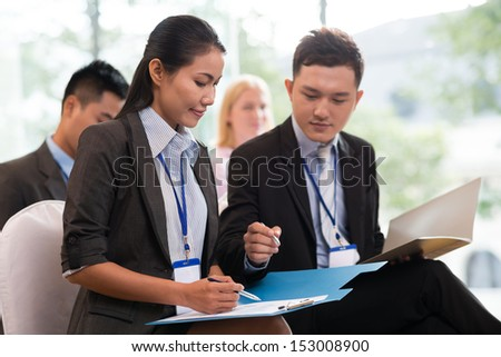 A couple of businesspeople discussing some data at the business meeting - stock photo
