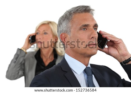 A couple of businesspeople over the phone. - stock photo