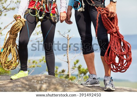 a couple of climbers with ropes on a cliff top. mountain climbing equipment - stock photo