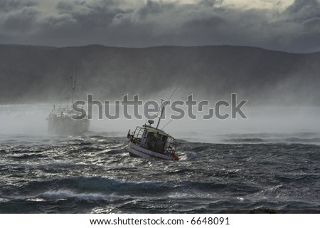 A couple of fishing boats in stormy seas. - stock photo