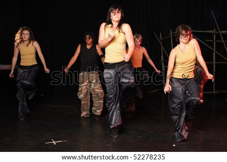A couple of freestyle hip-hop dancers during dance training session on stage. Lit with spotlights - stock photo