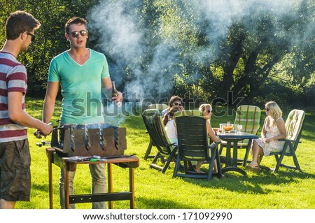 a couple of girlfriends relaxing in the sunny garden at the table with their boyfriends in the foreground stand besides the barbecue - stock photo