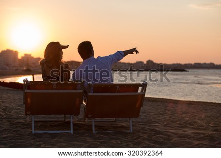 a couple of guys in the sea watching the sunset in silhouette. young people on vacation at sea. concept of two boys sports in perfect contact with nature. couple of guys arrived with the longboard.