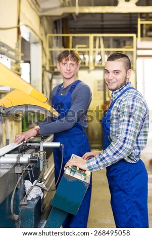 A couple of happy adult men around the milling machine - stock photo