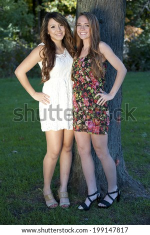 A couple of happy and young girls posing outdoors on a sunny day.