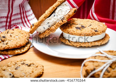 A couple of homemade ice cream sandwiches made out of two oatmeal and raisins cookies and chocolate chip ice cream in the middle, in a rustic kitchen