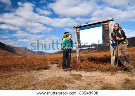 a couple of long distance hiker on a empty label in autumn - stock photo