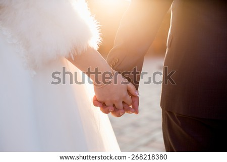 A couple of married people holding hands together. shot with warm colours under sunlight - stock photo