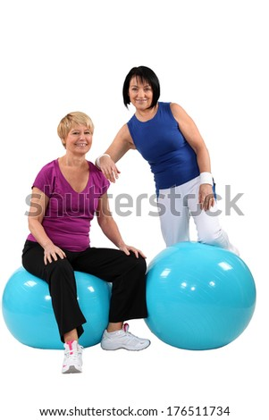 A couple of middle aged women working out. - stock photo