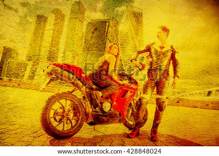 A Couple of Motorcycle Riders with their Custom Bike on yellow wall. - stock photo