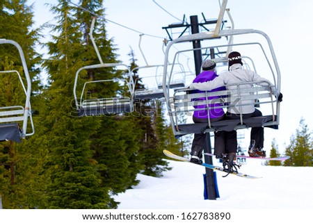 A couple of people ride the ski chair lift up the mountain together while sitting closely to each other having a fun time during a day of snowboarding in oregon. - stock photo