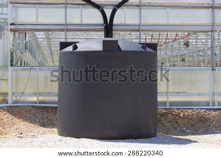 A couple of rain water collection tanks used to catch rain water off of a greenhouse.  - stock photo