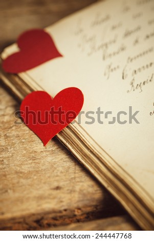 A couple of red heart shapes on a handwritten old journal.