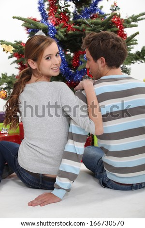 A couple of teenagers sitting in front of the Christmas tree. - stock photo