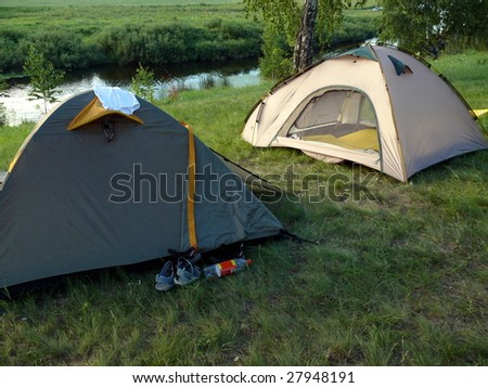 a couple of tent in river background - stock photo