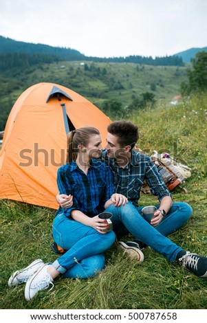 A couple of tourists in time of the hike, sit outside the tent, mountain scenery. The guy hugs the girl. The concept of love and recreation