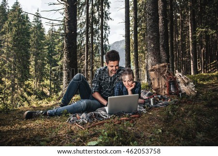 A couple of tourists lie on the blanket and looking at laptop in the woods. The concept of active rest