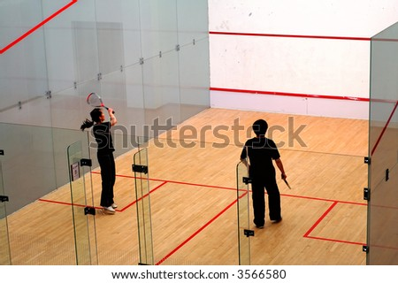 A couple of young boy and girl playing squash - stock photo