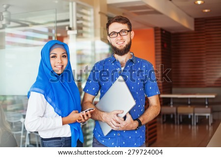 a couple of young entrepreneurs: muslim asian woman and a caucasian man - stock photo