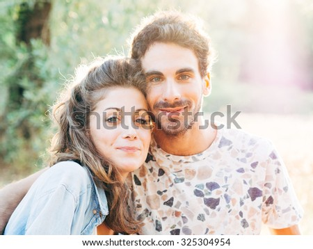 A couple of young lovers embracing each other at sunset, behind them the rays of the sun of late summer in the woods and fields planted with olive trees of the classic landscape of Tuscany, Italy
