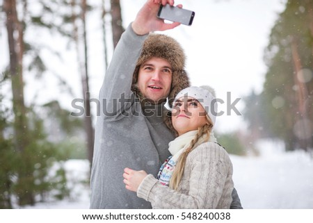 A couple on a walk in the woods in the snow, making self ie on smart phone