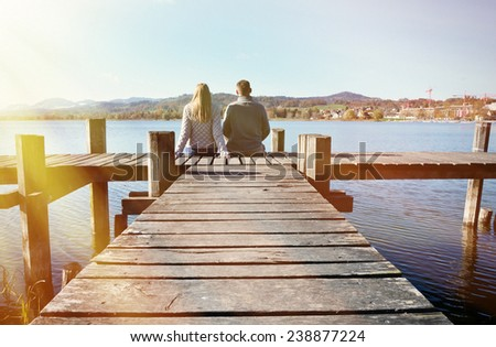 A couple on the wooden jetty at a lake - stock photo