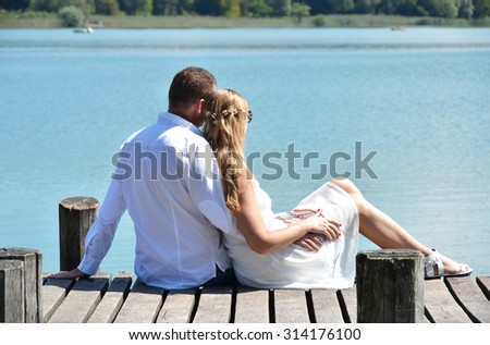 A couple on the wooden jetty at the lake. Switzerland - stock photo