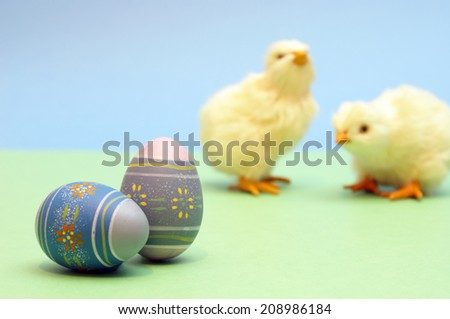 A couple painted eggs are in focus while a couple chicks are blurred in the background. - stock photo