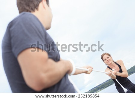 A couple play tug-of-war with rope. - stock photo