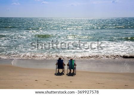 A couple relaxes on the beach in Kure Beach, North Carolina. - stock photo