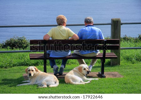 A couple relaxing looking out to sea whilst their dogs look the other way - stock photo