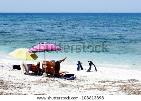 A couple relaxing on a beach under colorful umbrellas - stock photo