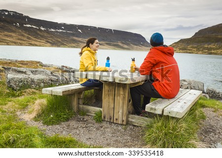 A couple resting close to a beautiful lake - stock photo