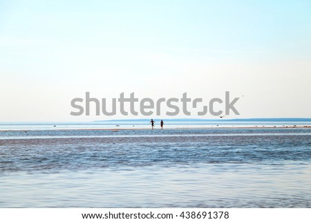 A couple running along the sea shore by water far off against the blue sky, sea and horizon - stock photo