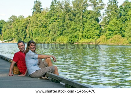 A couple, sit together on a dock, with their feet dangling over, smiling. - horizontally framed