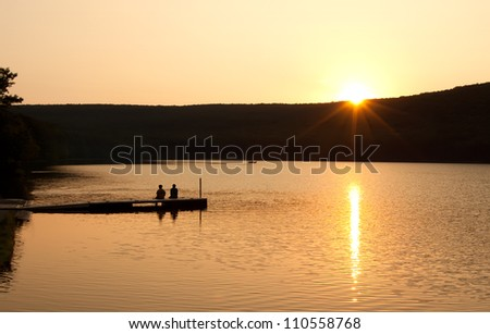 A couple sitting on a boat dock watching reflections on as the sun sinks over the mountain. - stock photo