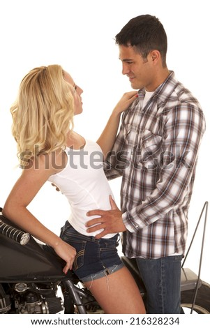 a couple sitting on a motorcycle looking and touching each other. - stock photo
