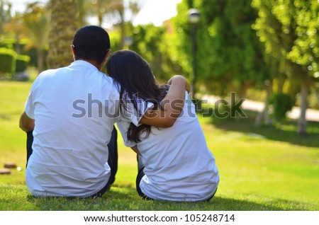 A couple sitting on grass thinking - stock photo